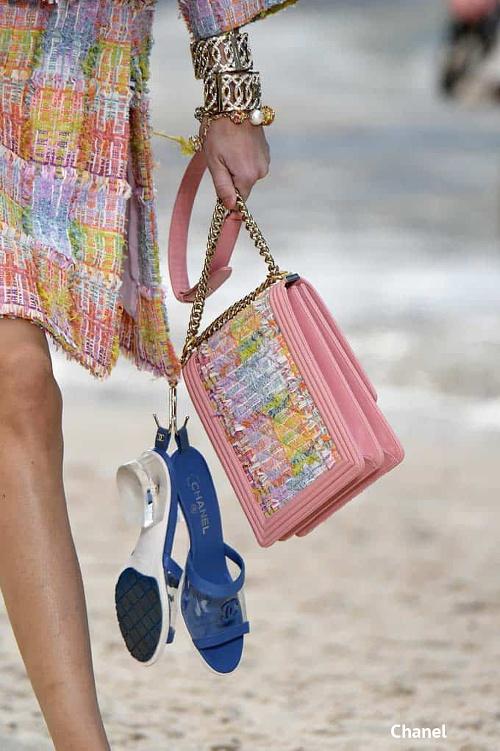 mała kolorowa torebka damska na łańcuszku Chanel w pastelowym różu w prezentowana na wybiegu z piasku