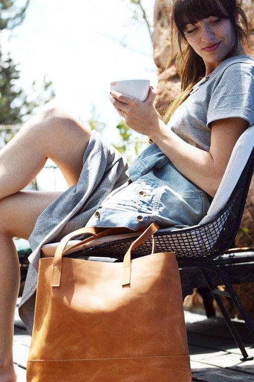 kobieta pijąca kawę i skórzana torebka damska brązowa