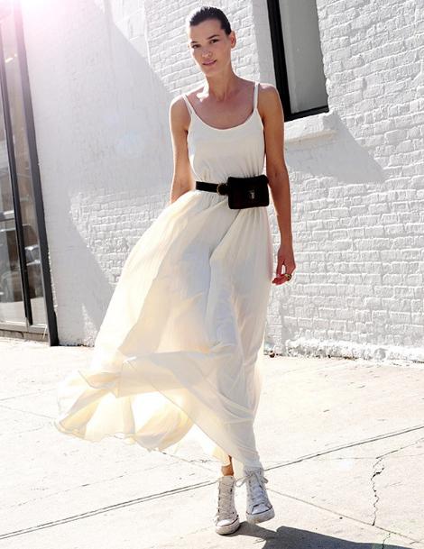kobieta w białej sukience i białych trampkach z czarną torebką na pasku, nerką