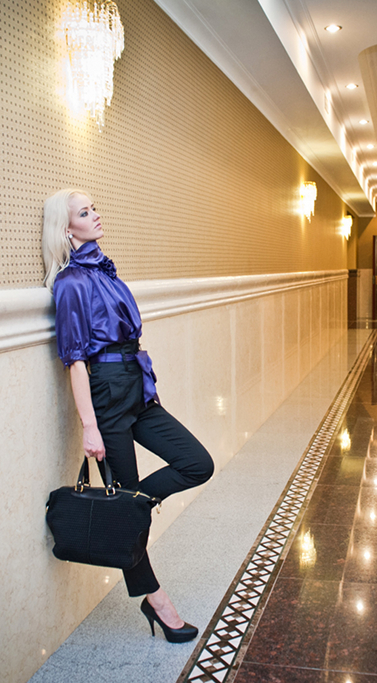 elegancka czarna torebka kuferek w ręce eleganckiej kobiety w stylowym wnętrzu