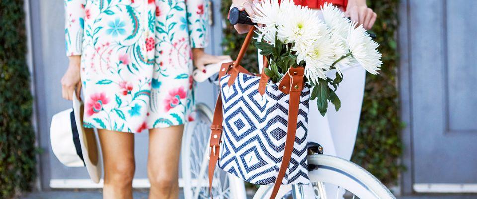 biała torebka z niebieskim wykończeniem i kobieta na rowerze z kwiatami