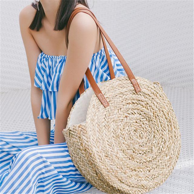 torba plażowa okrągła pleciona w jasnym kolorze i kobieta ubrana w kombinezon w marynarskie pasy