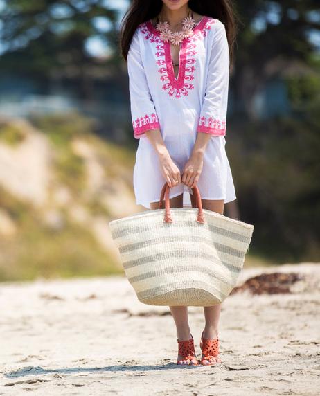 torebka z rafii duża w rękach kobiety w białej tunice i pomarańczowych sandałach