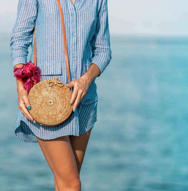 okrągła torebka z rafii przewiązana apaszką nad brzegiem oceanu kobieta w niebieskiej koszuli